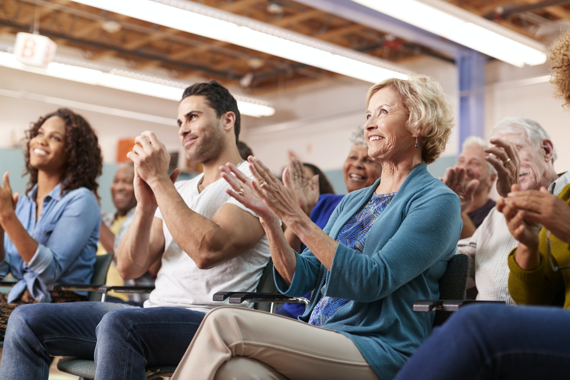 Group Attending Neighborhood Meeting In Community Center Clapping